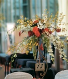 Iron stand holding table number and flowers