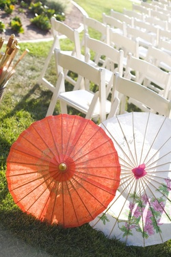 Orange and white paper parasols for wedding guests