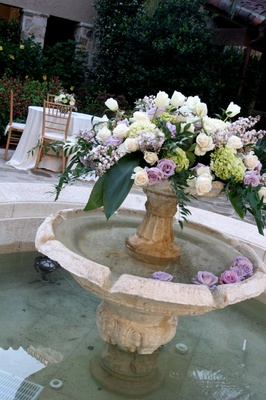 Fountain decorated with light purple and white roses, green hydrangeas, and white tulips