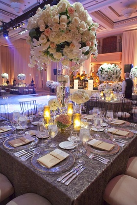 Wedding reception table with a tall centerpiece of light flowers surrounded by low arrangements