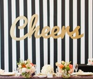 Wedding shower backdrop with black and white stripes and the word Cheers in gold letters