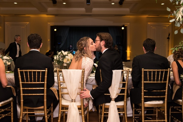 bride and groom kiss at head table, bride and groom's seats marked with ivory fabric
