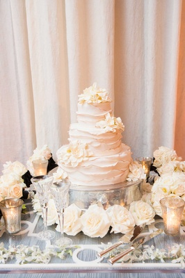 White three tier wedding cake with ruffle details, fresh gardenia flowers, roses at base, candles