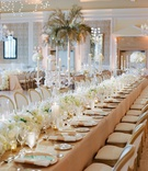 Wedding reception long table beige linen white flower runner crystal candelabra white wood chairs