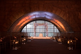 dimly lit ceremony space featuring a white chuppah and stage with cherry blossoms