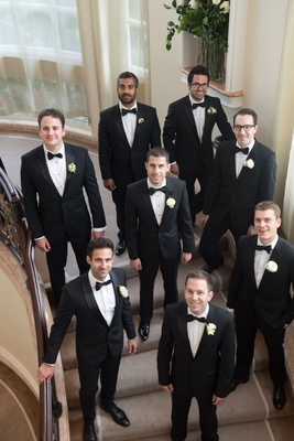 Groom in middle of groomsmen on stairs at the beverly hills hotel tuxedos and bow ties white flowers