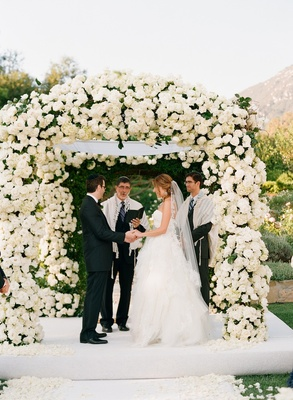 Bride and groom stand under white flower ceremony structure