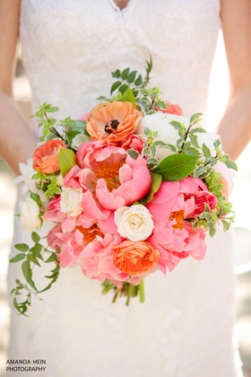 Coral charm peonies come together with rich spring blooms for a stunning bridal bouquet.