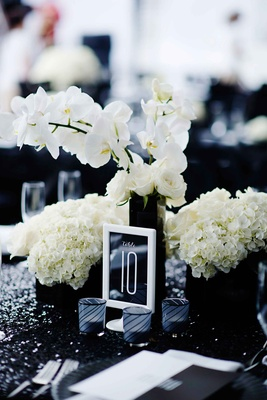 White frame with table number on black stationery at wedding