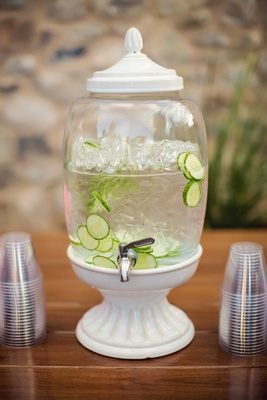 White drink dispenser with silver spout, ice water with sliced cumbers