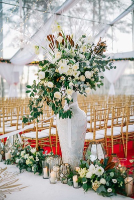 wedding ceremony red carpet gold chairs white aisle runner greenery white flowers candles