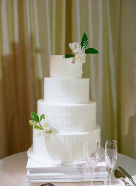wedding cake four layers round tier with fresh flowers on top and bottom layer swiss dot ribbon