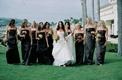 Bride with nine bridesmaids on grassy lawn