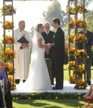 Bride and groom at yellow ceremony structure