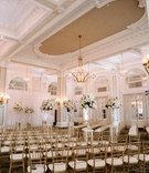 ornate molding at ballroom in atlanta gold chairs tall flower arrangements along aisle white drapery