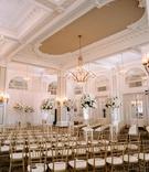 ornate molding at ballroom in atlanta gold chairs tall flower arrangements along aisle white drapery