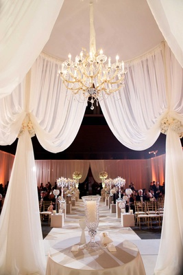 Wedding ceremony structure with ivory drapery, flower tiebacks, and crystal chandelier