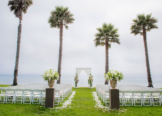 wedding ceremony on grass lawn overlooking beach ocean palm trees lily flowers in stone urn drapery