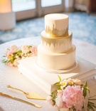 Three layer wedding cake round tiers layers gold brushstroke details pink flowers sequin table