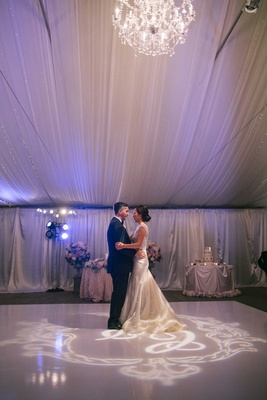Bride in reception wedding dress with groom during first dance at tent wedding with purple lighting