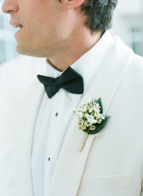 Groomsman in White Tuxedo Jacket with Lily of the Valley boutonniere black bow tie
