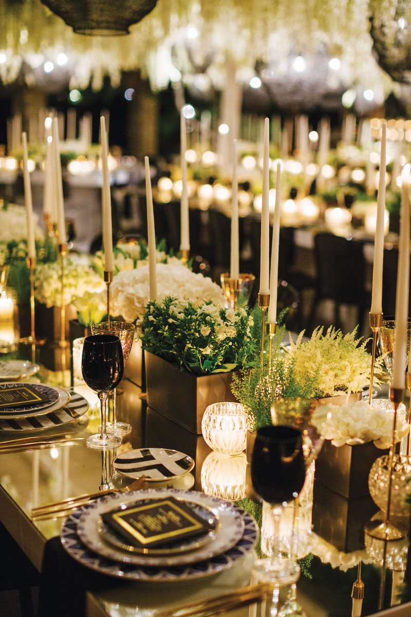 wedding reception modern black white geometric designs taper candles greenery black glassware goblet