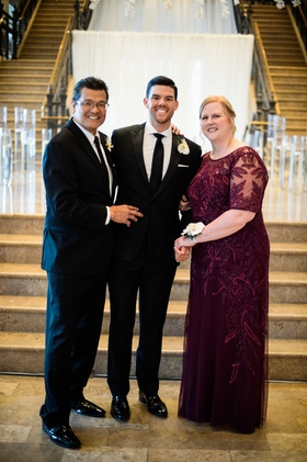 groom with father and mother in burgundy dress sheer detail beading white flower corsage on wrist