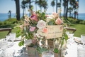 Oceanfront wedding reception table with white, peach, pink roses, white hydrangeas, red protea,