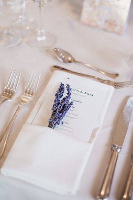 wedding reception place setting with a printed menu and sprigs of lavender tucked into ivory napkin