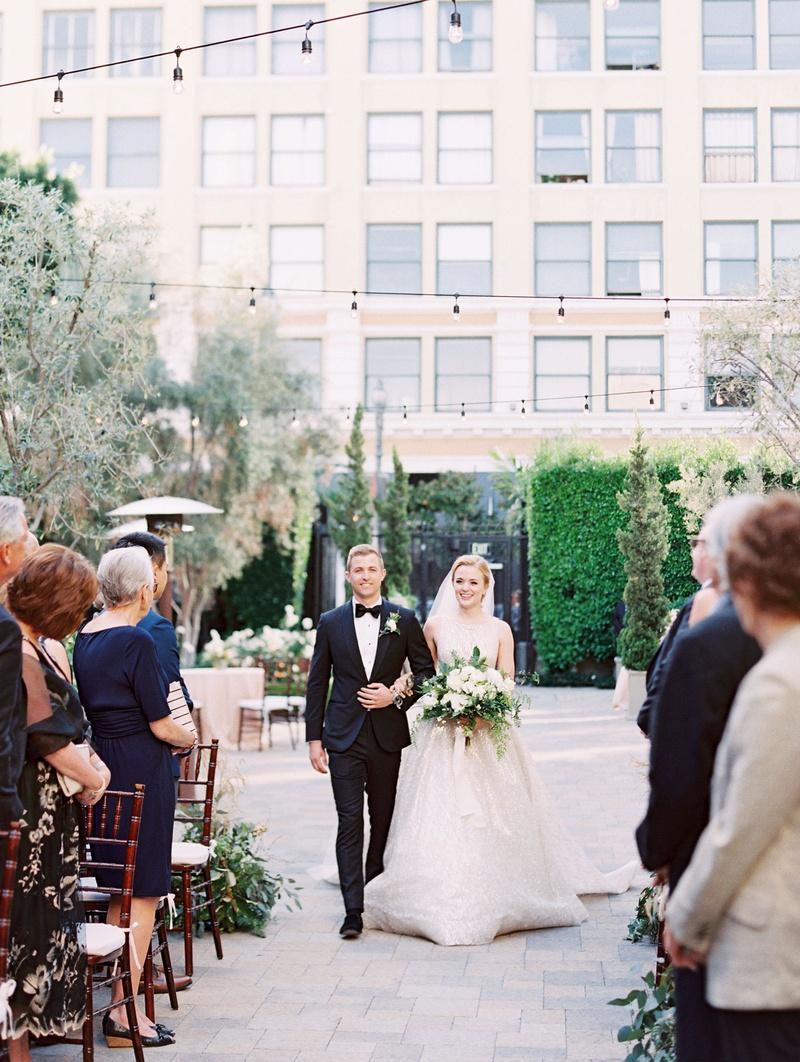 bride in high neck lazaro wedding dress escort in tuxedo bow tie bistro lights overhead vibiana