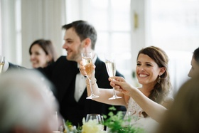 Wedding reception long reception tables toasting champagne glasses flutes in air