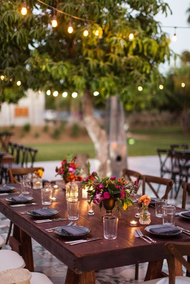 destination wedding, small arrangements with dark pink flowers, dark wood tables