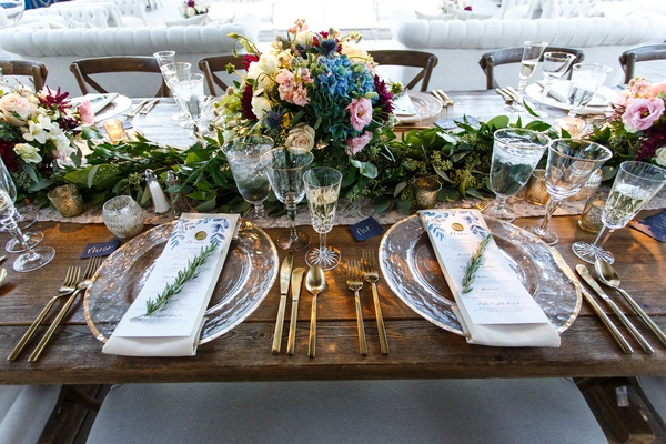 wood table with gold flatware charger plate sprig of rosemary menu card low centerpiece vineyard