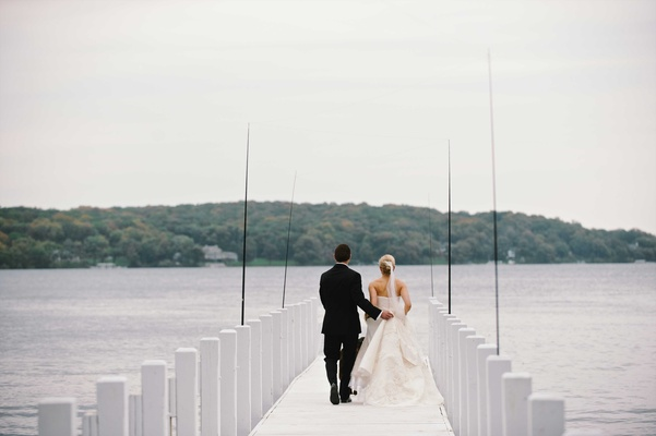Bride in a strapless Vera Wang dress, updo, veil walks with groom in black tuxedo on Lake Geneva
