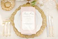 Wedding reception place setting with a gold charger, flatware, and pink napkin