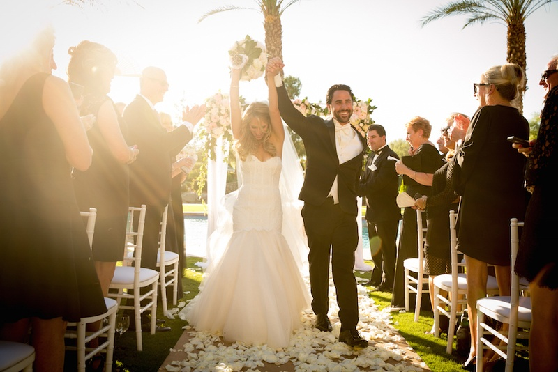 Bride and groom raising hands in celebration up aisle