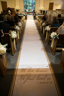 aisle runner with gold trim and 1 john 4:19 verse on aisle runner