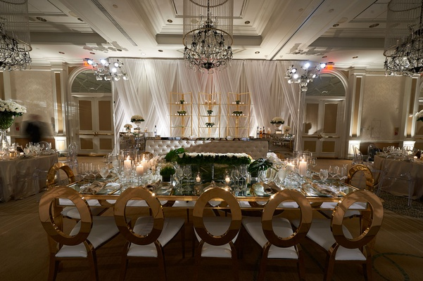 wedding reception tufted bar gold shelves mirror table gold chairs low centerpiece