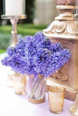 Wedding reception table with bright purple hyacinths in a clear vase with gold rims
