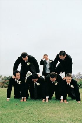 Groom and groomsmen set up a human pyramid