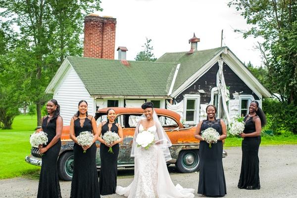 bride in eddy k wedding dress, bridesmaids in lulus black dress