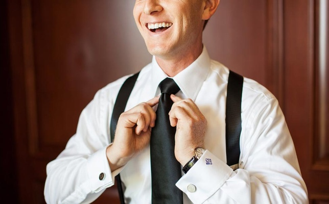 Groom getting ready and tying black tie