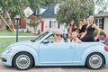 bride and bridesmaids riding in light blue VW beetle convertible