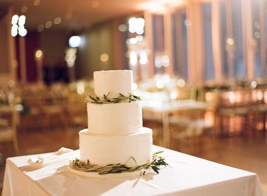 simple three-tiered white wedding cake with greenery at modern wedding
