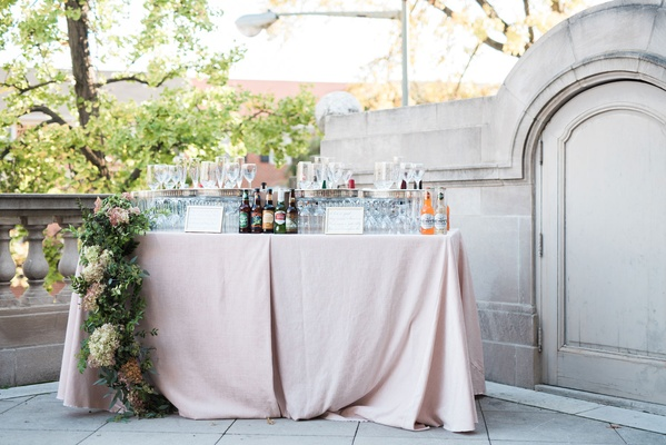 Wedding reception cocktail hour pink linen tablecloth bar area with beer and flower runner