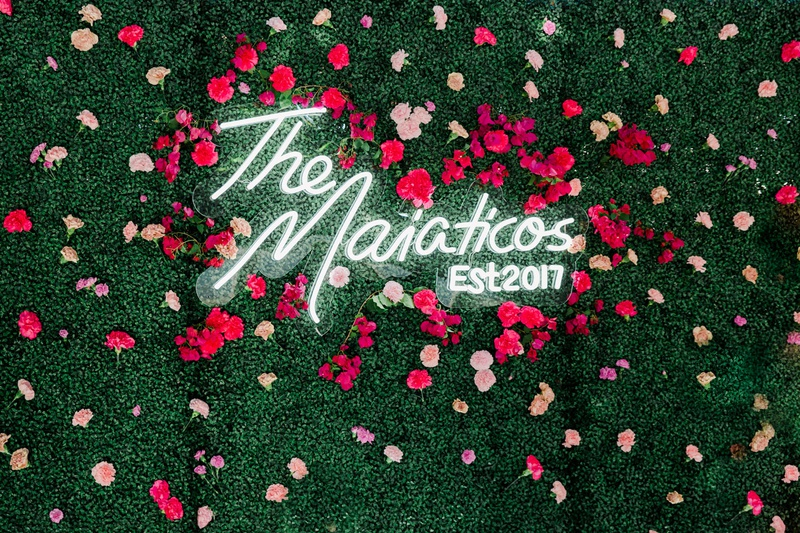 wedding reception hedge wall with pink rose flowers custom neon sign with new last name established
