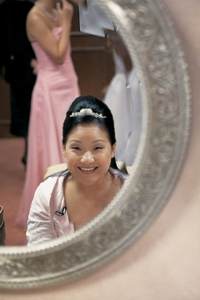 bride with updo hairstyle looking in mirror