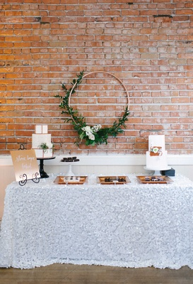 a dessert table textured white table linen copper signage white cakes hoop greenery geometric shapes