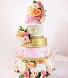 wedding cake with gold layer monogram pink draped watercolor design fresh flowers