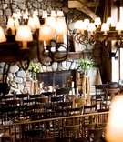 lodge with wooden chairs, stone fireplace and rustic lampshade chandeliers